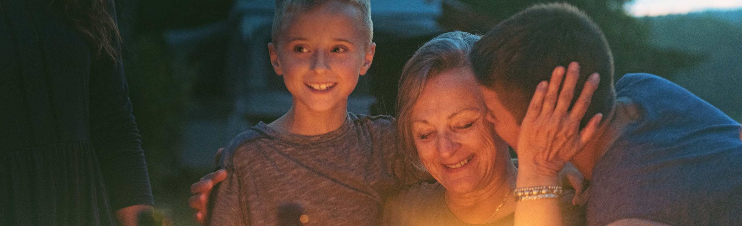 Woman with grandkids near campfire