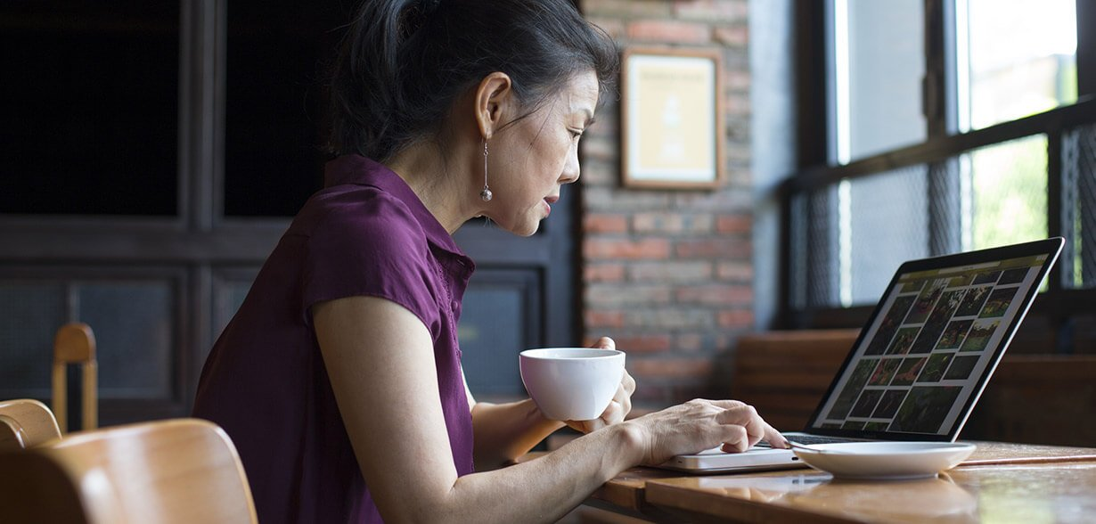 Woman drinking coffee while working on laptop computer